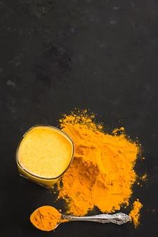 Latte alla curcuma, una bevanda salutare calda lattiginosa dorata su uno sfondo scuro in un bicchiere di vetro