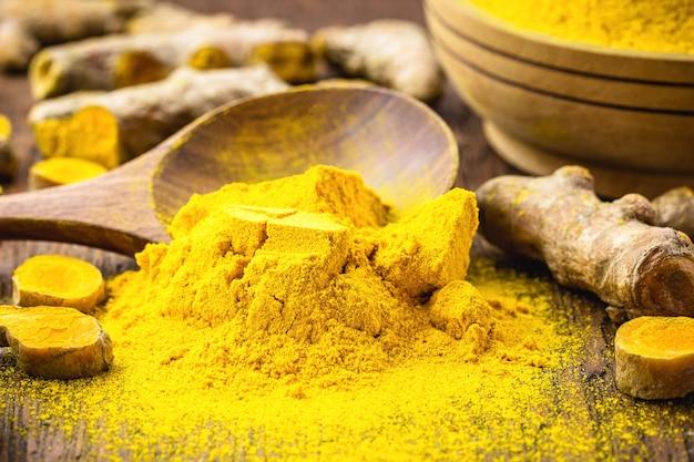 Curcuma in polvere o curry in un cucchiaio di legno rustico, polvere sparsa sul tavolo, fotografia macro di cibo