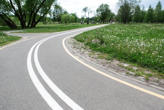 Giro della pista ciclabile nel parco primaverile. strada vuota.