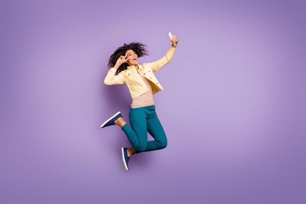 Girato la foto di dimensioni del corpo a figura intera della ragazza eccitata pazza allegra in pantaloni pantaloni che mostra vsign prendendo selfie che salta i capelli castani ondulati ricci isolati isolato sfondo di colore viola pastello