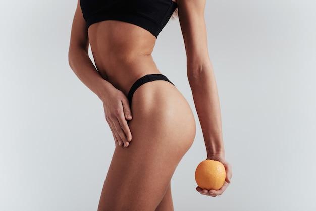 Parte sinistra girata. foto di particelle di ragazza in biancheria intima nera in piedi al muro bianco e tenendo l'arancia.