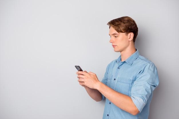 Foto girata del ragazzo lavoratore concentrato utilizza smartphone in chat con i colleghi clienti sui social media tipo di testo sms indossare un bell'abbigliamento isolato su sfondo di colore grigio