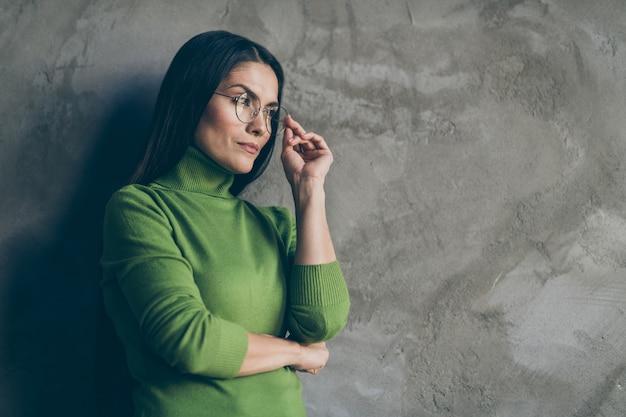 Foto girata di donna seria sicura che si appoggia sulla priorità bassa concreta del muro grigio che è isolata sopra toccare i suoi occhiali che guardano lontano