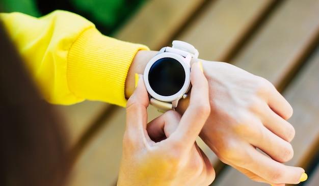 Girando smartwatch. un primo piano da dietro di una ragazza con una felpa con cappuccio gialla, con un moderno smartwatch bianco, che lo accende con due dita.