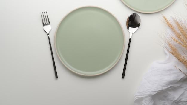 Piatti in ceramica turchese, argenteria, tovagliolo e grano dorato decorati sul tavolo da pranzo