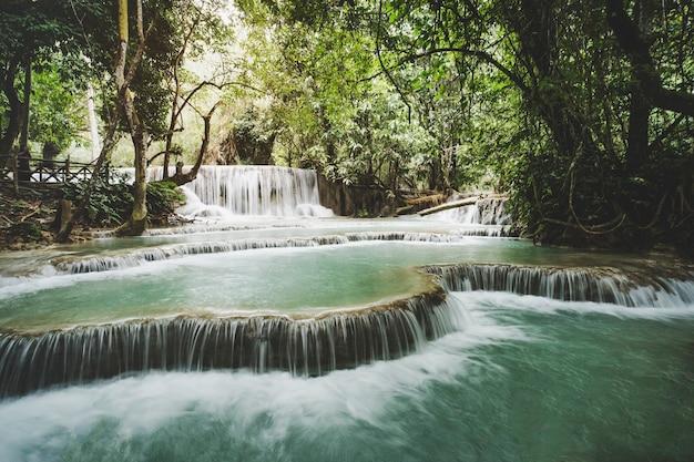 Acqua turchese della cascata di kuang si, luang prabang. laos. esposizione prolungata. bellissimo paesaggio. cascata nella giungla selvaggia. natura asiatica. cascata di piccole cascate.