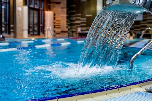 Una cascata turchese, massaggio schiena e spalle in piscina.