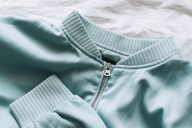 Giacca da donna turchese con zip, primo piano.