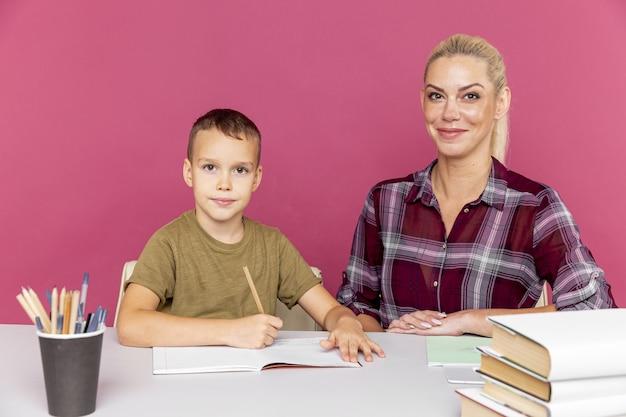 Tutor con bambino che fa i compiti insieme nella stanza rosa.