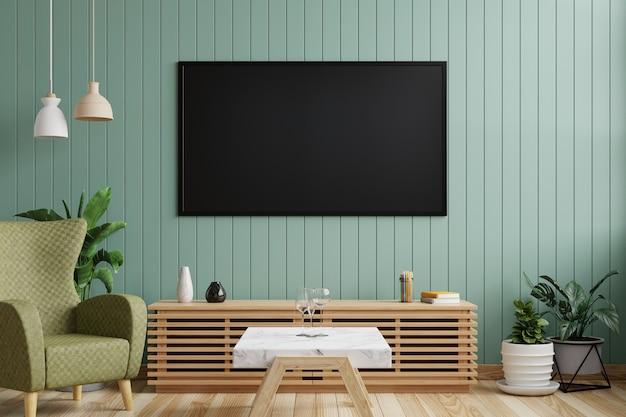 Tv sulla parete di legno verde nel soggiorno decorato con poltrona, mobile in legno e piante sul pavimento