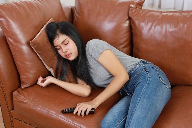 Tv e concetto di felicità. bella donna asiatica in casual sdraiata sul divano in soggiorno, tenendo il telecomando della televisione e dormendo mentre si guarda la televisione con una faccia sorridente felice. concetto di stile di vita.