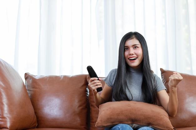 Tv e concetto di felicità. bella donna asiatica in casual seduta sul divano in soggiorno, tenendo il telecomando della televisione e guardando qualcosa con una faccia sorridente felice. concetto di stile di vita.