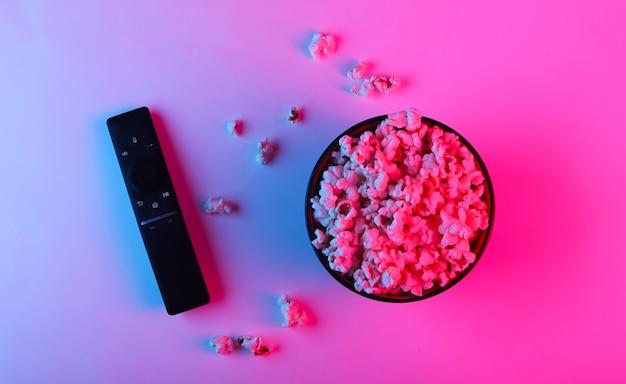 Telecomando della tv e ciotola di popcorn.