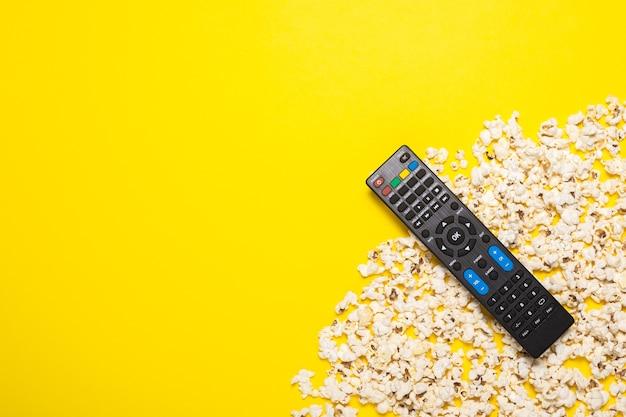 Telecomando tv, sintonizzatore tv o sistema audio e popcorn in giallo