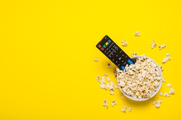 Il telecomando della tv, il sintonizzatore tv si trovano in una ciotola con i popcorn sul giallo