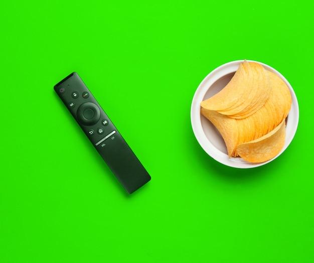 Telecomando della tv, patatine fritte in un piatto su priorità bassa verde