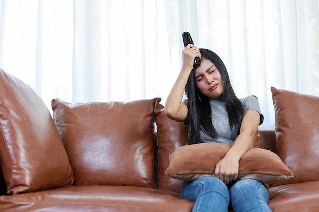 Tv e concetto di tristezza. bella donna asiatica in casual seduta sul divano in soggiorno, tenendo il telecomando della televisione e guardando qualcosa con una faccia sorridente felice. concetto di stile di vita.
