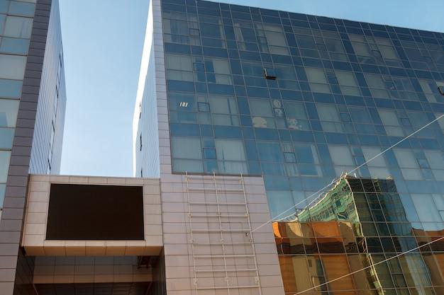 Schermo tv su edificio aziendale. grande schermo nero vuoto del tabellone per le affissioni del layout tv. modello per inserire annunci sulla parete di un edificio moderno. schermo principale vuoto grande tabellone per le affissioni nero sull'edificio