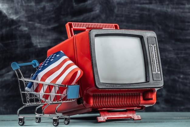Supermercato televisivo. carrello della spesa con bandiera usa, televisore retrò su sfondo lavagna