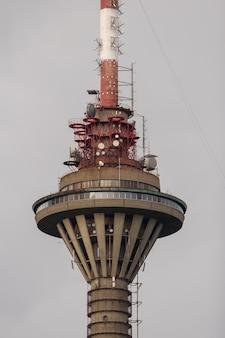 Torre della tv nella città di tallinn contro il cielo grigio con molte antenne e trasmettitori