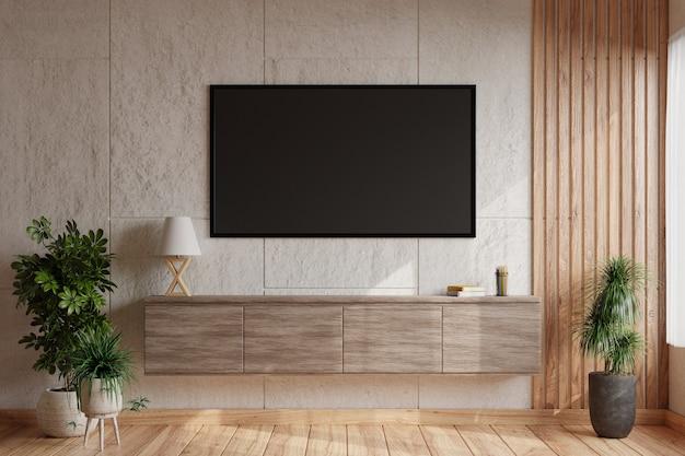 Tv su un muro di cemento bianco in un soggiorno moderno con una lampada e libri posizionati su un mobile in legno e decorato con un vaso per piante sul pavimento in legno. rendering 3d.
