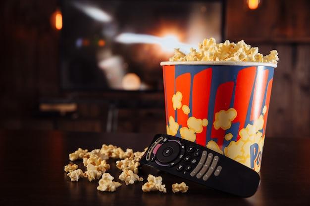 Tv con il concetto online di amici. guardando film e mangiando popcorn nella ciotola.