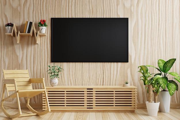Tv sulla parete in legno del soggiorno decorata con piante e sedia a dondolo