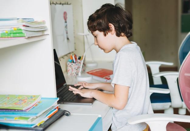 Il ragazzo di tween fa i compiti impara la lingua straniera scrivendo nel libro della pupilla con il computer portatile aperto all'istruzione domestica della dittanza della stanza