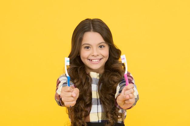 Due volte più veloce. ragazza carina capelli lunghi tiene spazzolini da denti sfondo giallo. la ragazza del bambino tiene due spazzolini da denti. bambino scuola ragazza bambino intelligente faccia felice si prende cura dell'igiene. spazzola i denti concetto. igiene dei denti.