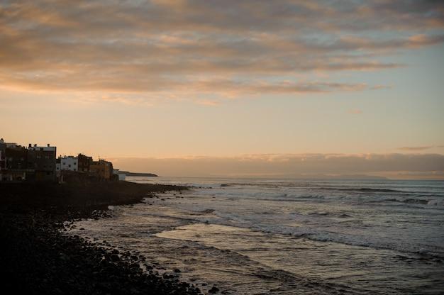 Crepuscolo sopra la bellissima città antica e la costa del mare con onde sotto il cielo e le nuvole