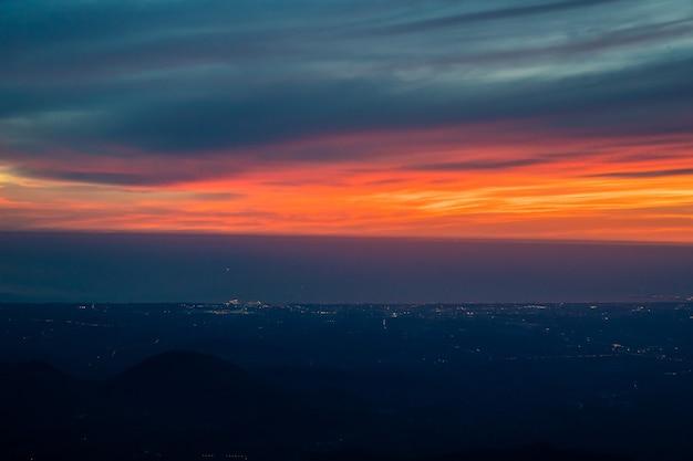 Crepuscolo alla notte dal cielo blu arancio rosso di vista dell'aereo a reazione con la luce della città della tailandia qui sotto