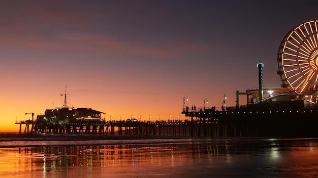 Oceano crepuscolare e ruota panoramica illuminata, parco di divertimenti sul molo. spiaggia di santa monica, usa.
