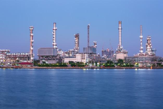 Scena crepuscolare della raffineria di petrolio della riflessione dell'acqua della parte anteriore dell'industria petrolchimica.