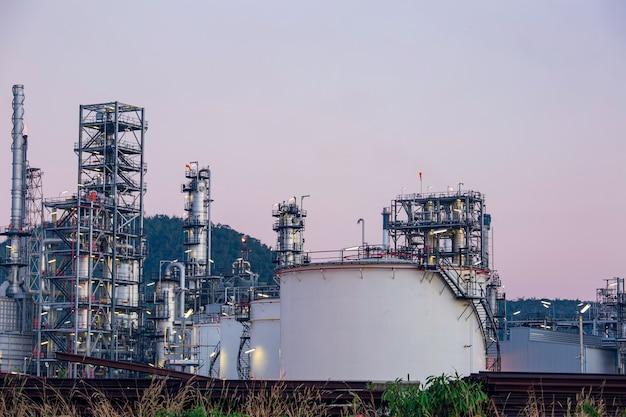 Scena crepuscolare dell'impianto di raffineria di petrolio del serbatoio e della colonna della torre dell'industria petrolchimica nella costruzione del sito