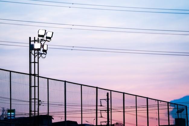 Cielo crepuscolare sopra il campo di calcio con silhouette sportlight