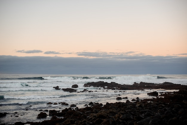 Crepuscolo sopra la costa ondeggiante del mare con pietre selvagge in serata ventosa sotto il cielo