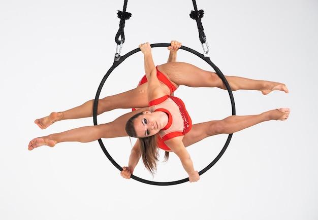 Artista di circo femminile dei gemelli sul cerchio aereo isolato su bianco. ginnaste molto flessibili e professionali.