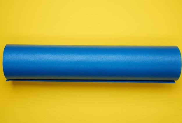 Tappetino in neoprene blu ritorto per yoga e sport su una superficie gialla