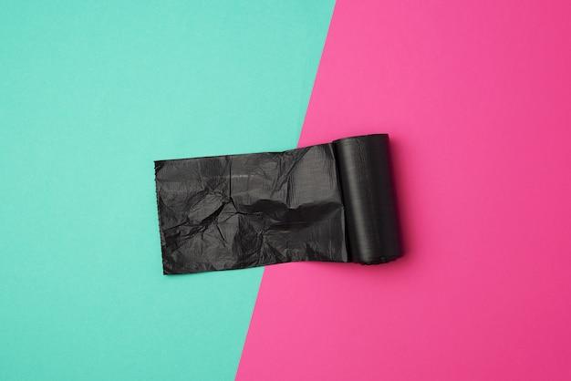 Rotolo contorto con sacchetti di immondizia neri su un colorato