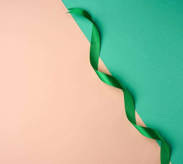 Nastro verde seta contorto su una superficie verde-beige