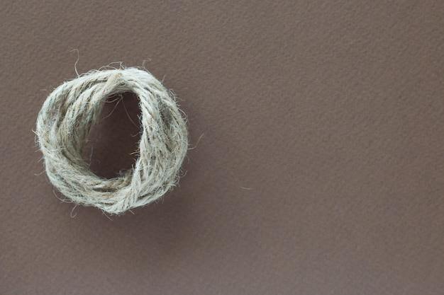 La corda bianca contorta su fondo marrone
