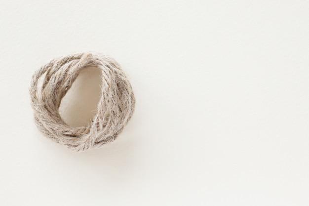 La corda bianca attorcigliata su fondo bianco