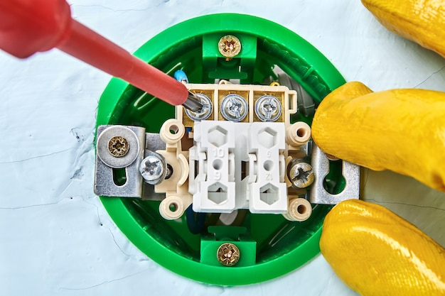 Torcendo la vite nel nuovo pulsante con l'aiuto del cacciavite, manutenzione elettrica.