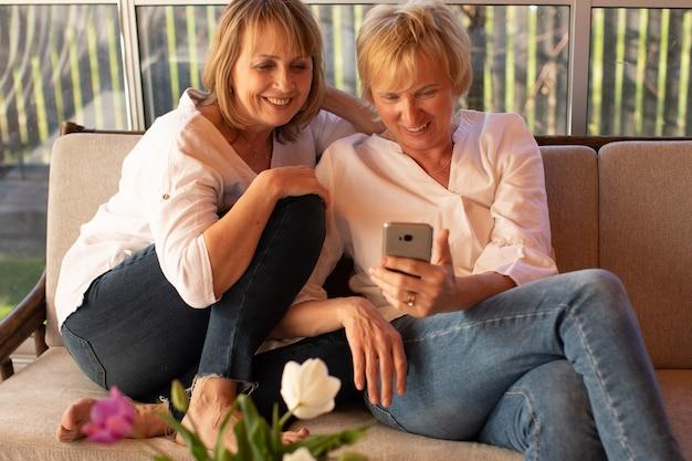 Due signore mature di 55 anni che si divertono usando il dispositivo mobile, concetto di amicizia femminile