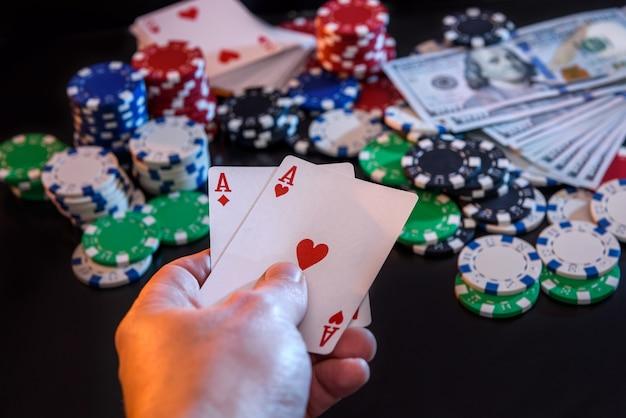 Due assi in mano e gettoni da gioco al nero
