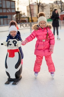 Due adorabili bambine che pattinano sulla pista di pattinaggio