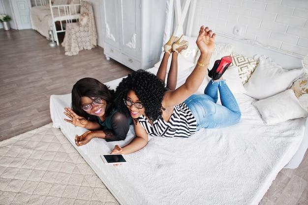 Due amici africani della donna indossano gli occhiali che si trovano sulla stanza bianca dell'interno del letto e che esaminano il telefono cellulare.