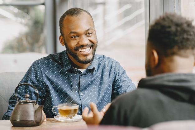 Due uomini afroamericani che conversano con una tazza di tè. amico seduto in un caffè.