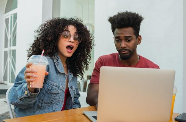 Due amici di afro che per mezzo del computer portatile ad un self-service.