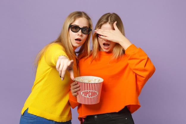 Due giovani sorelle gemelle bionde stupite in occhiali 3d imax che guardano film in possesso di popcorn isolato su parete blu viola pastello. concetto di stile di vita familiare di persone.